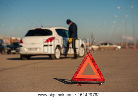 Upset Young Man Checking Wheel After Car Breakdown