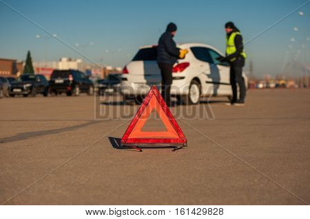 Male driver talking with car assistance technician. Mechanic checking auto after breakdown. Red triangle sign foreground.