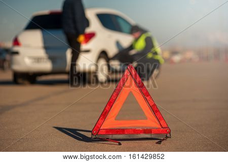 Car assistance technician checking the wheel after breakdown. Male driver staying next to auto. Red triangle warning sign foreground.