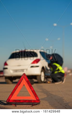 Car after breakdown on parking. Road assistance technician and male driver changing flat tire outdoors. Red emergency warning sign foreground.