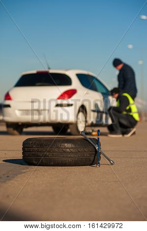 Car repairman and young driver after breakdown. Spare wheel and wrench foreground.