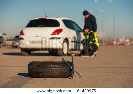 Wheel wrench and tyre on the background of car assistance technician and male driver. Fall or winter sunny day.