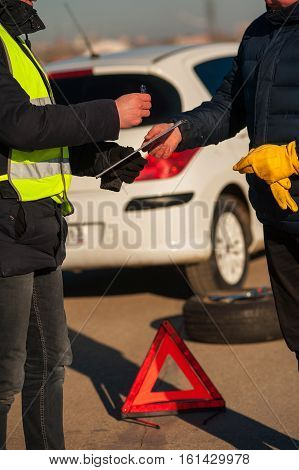 Car assistance technician checking auto and writing on clipboard. Car breakdown. Red emergency sign spare wheel and wrench.