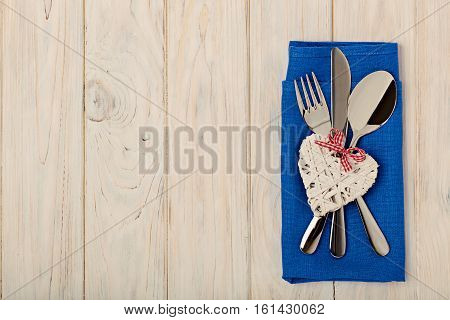 Valentine's day concept. On the wooden table cutlery on linen napkin with the decoration of heart.