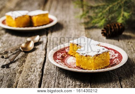 Homemade moist pumpkin pie dusted with powdered sugar and chopped slices on patterned plates on the shabby wooden background with branches of spruce and pine cones. Selective focus
