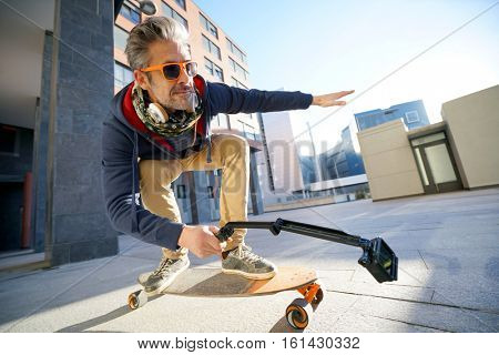 Mature man skateboarding in urban environment, filming himself