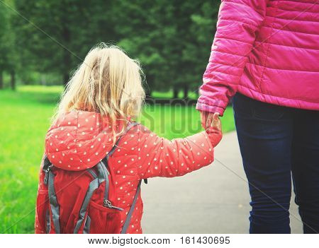mother walking little daughter to school or daycare, kids learning