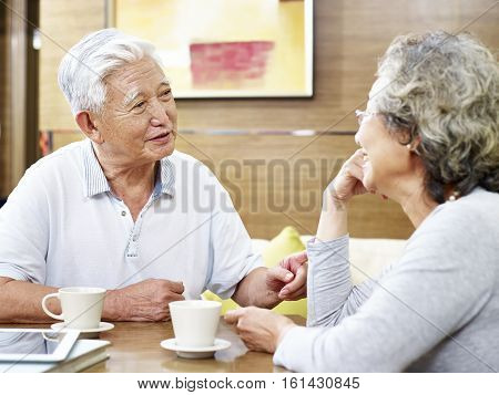 loving senior asian couple drinking coffee and chatting