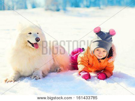 Little Child And White Samoyed Dog Lying On Snow Winter