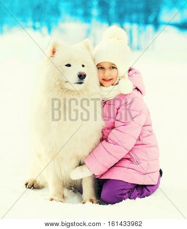 Portrait child embracing white Samoyed dog on snow winter
