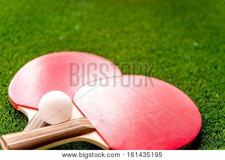 red racket for ping pong ball on green background close up