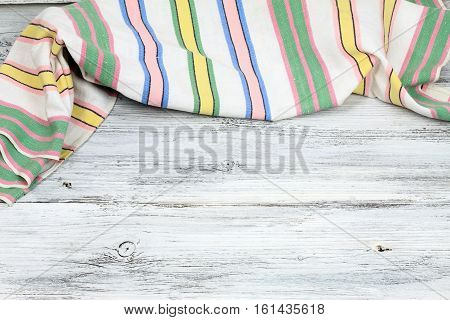 Dish cloth with stripes on wooden table. Linen tea towel on board good for background
