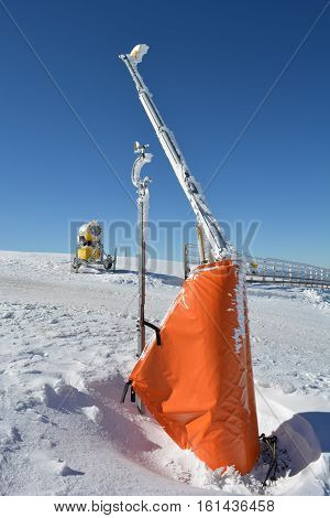Start of the ski slopes with ramp high wooden fence snow cannon and meteorological wind gauge mounted on the ramp vertical orientation Kopaonik Serbia