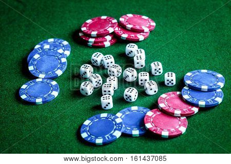 poker chips and dice on green background close up