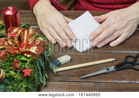 Handmade - Female hands are folding paper tree on wooden desk