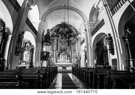 GRAZ AUSTRIA - FEBRUARY 15 2016: Interior of the Holy Trinity Church. Empty seats with beautiful altar. Small church in the city center