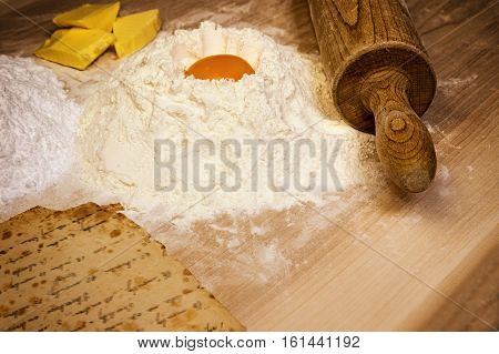 Vintage photo of pile of flour with egg yolk on the top pile of sugar butter and wooden rolling pin on the wooden desk. Old vintage paper with intentionally blurred script is in the left lower corner of the photo.