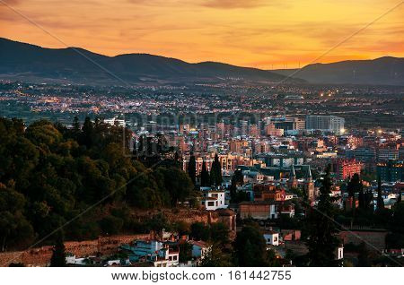 Granada Spain. Aerial view of Granada - famous city in Andalusia Spain at night with mountains at the background. It is a UNESCO World Heritage Site and a major touristic attraction
