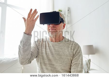 technology, augmented reality, gaming, entertainment and people concept - senior man with virtual headset or 3d glasses playing videogame and looking at his hand at home