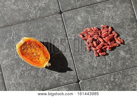 Prickly pear and goji berries, closeup on gray tiles