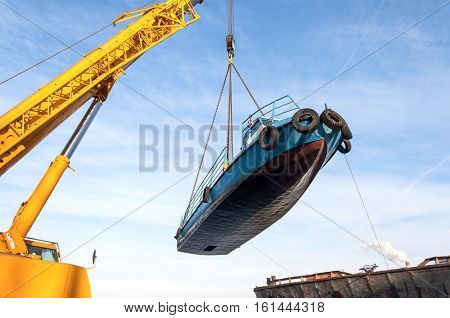 MOSCOW, RUSSIA - NOVEMBER 11, 2016: State Unitary Enterprise Mosvodostok performs recovery vessels on coastal winter parking. The ship hanging in the slings under the boom of the crane car.