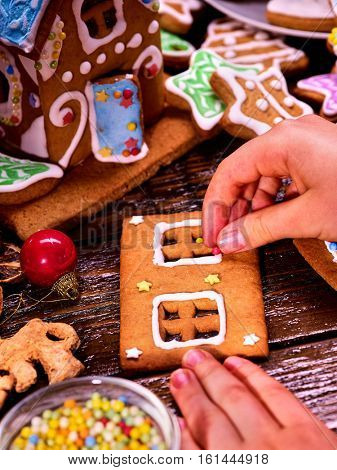 Child makes gingerbread house for Christmas. Christmas cookies and ready-made gingerbread house in background.