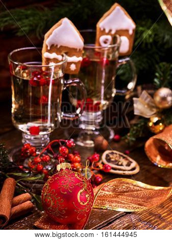 Close up Christmas still life with pair mug hot drink. Warming mulled wine with cookie in form of house and Christmas ball on foreground.