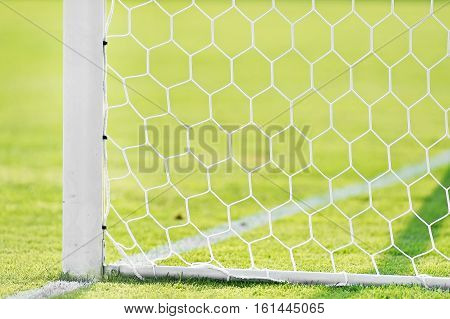 Soccer goal post and net detail on green turf