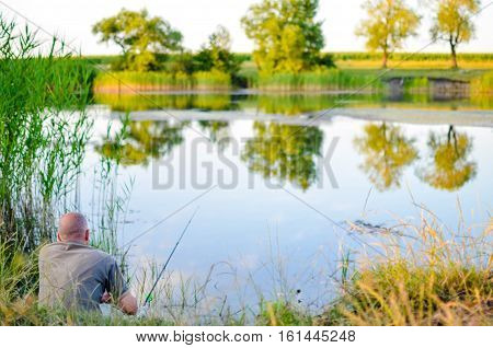 Fishman sitting at the lake in summer