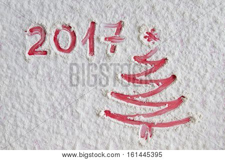 Red Christmas tree on flour background. White flour looks like snow. Top view