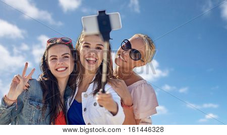 summer vacation, holidays, friendship, technology and people concept- group of smiling young women taking picture with smartphone on selfie stick over blue sky and clouds background