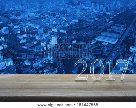 Happy new year 2017 text on wooden table over aerial of modern city tower street and expressway