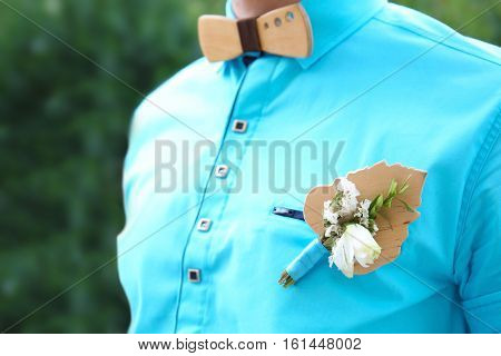 Best man in turquoise shirt with stylish boutonniere, close up