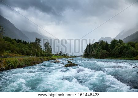 Norwegian landscape with milky blue glacier river Oldeelva in Oldedalen valley near Jostedalsbreen glacier