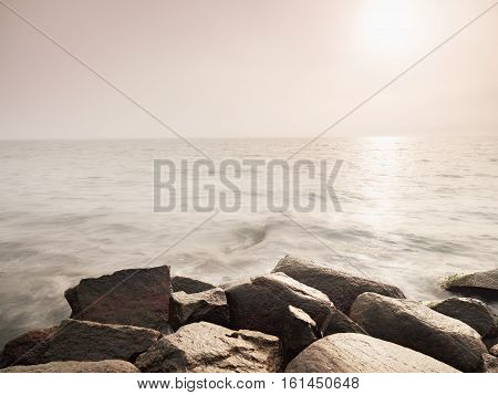 Big Wet Boulders In Shore In Smooth Wavy Sea. Stony Coast Defies To Waves