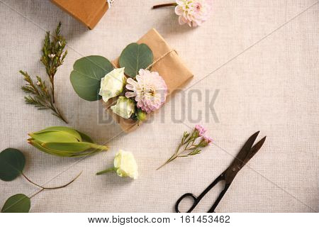 Handcrafted gift box with flowers and scissors on table