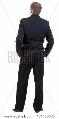 back view of adult man in black suit  watching.   Businessman looks ahead.  Isolated over white background. Rear view people collection. backside view of person.