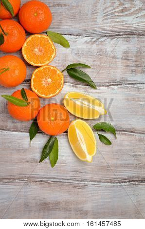 Fresh tangerine clementine and lemons with leaves on wooden background, top view, copy space