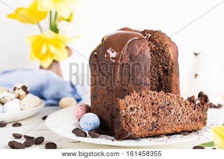 Easter orthodox sweet chocolate bread and colorful quail eggs on white background. Easter holidays breakfast concept with copy space.