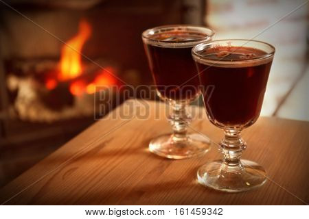 Glasses of mulled wine on wooden table against blurred fireplace