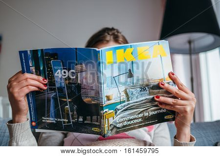 PARIS FRANCE - AUGUST 24 2014: Woman reading IKEA Catalogue before buying furniture for her new house