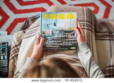 PARIS FRANCE - AUGUST 24 2014: View from above of woman reading IKEA Catalogue - admiring the cover before buying furniture for her new house. The catalogue is published annually by the Swedish home furnishing retailer