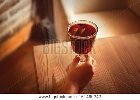Female hand and glass of mulled wine on wooden table