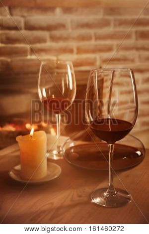 Decanter, glasses with red wine and candle on wooden table against fireplace