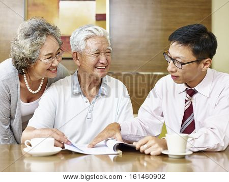 senior asian couple listening to a sale representative happy and smiling