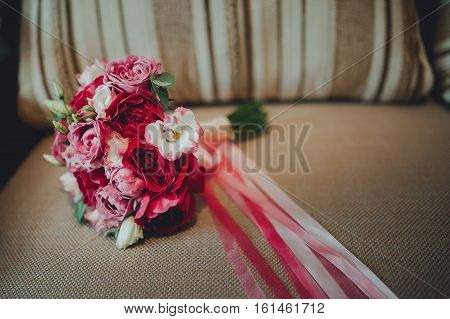 bridal bouquet of roses lying on the sofa