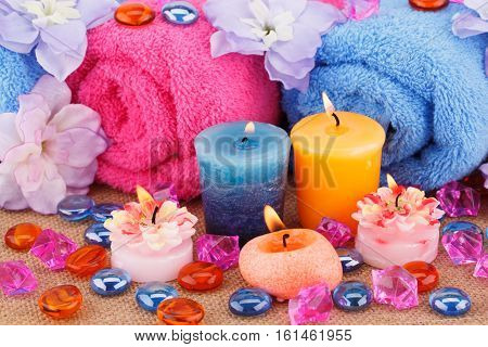 Spa set with towels candles stones and flowers on canvas background.