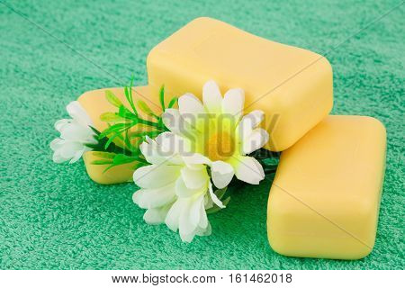 Yellow soaps and flowers on green towel.