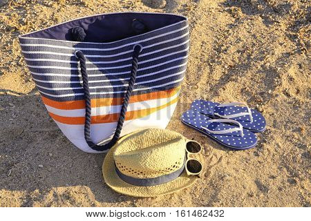 Beach bag with hat, sandals and sunglasses on sea coast