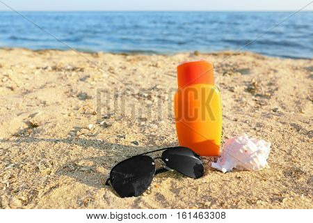 Sunglasses, shell and sunscreen cream on sea coast